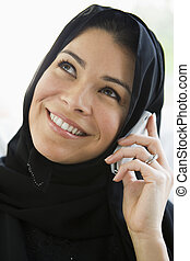 Woman indoors on cellular phone smiling (high key)
