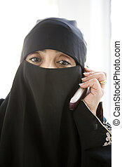 Woman indoors on cellular phone wearing veil (high key)