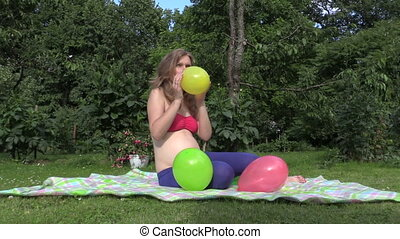 woman inflate balloon - Pregnant woman girl inflate colorful...