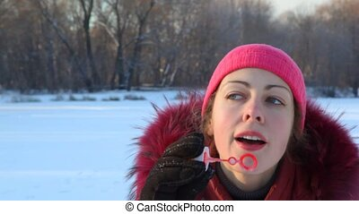woman inflates soap bubbles in wintry park - beautiful young...