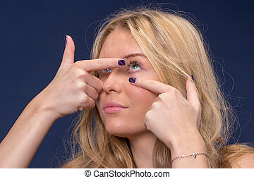 woman inserting contact lenses