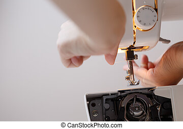 Woman inserts thread in sewing-machine