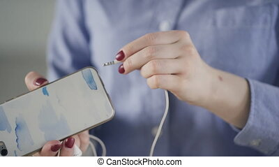 Woman inserts white earphones in mobile phone in office....