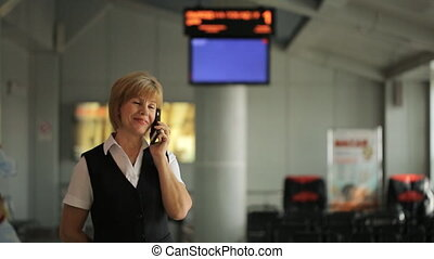 Woman inside waiting room at airport talking on phone....