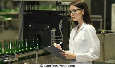Woman inspecting bottles at the factory - Conveyor with beer...