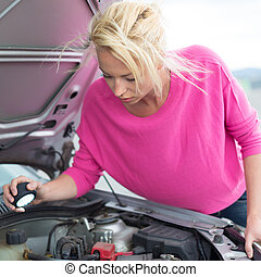 Woman inspecting broken car engine. - Self-sufficient ...