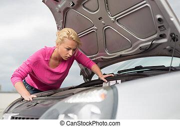Woman inspecting broken car engine.