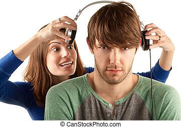 Woman interupts man with headphones