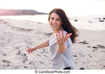 Cheerful woman inviting you to run with her along the sandy shore
