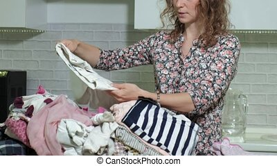 woman ironing a mountain of laundry at home in the kitchen