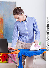 Woman ironing clothes and checking email on her laptop
