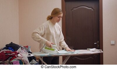 Woman ironing clothes board iron home interior watch TV