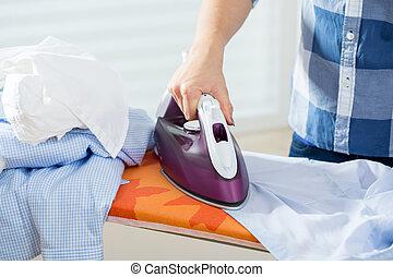 Woman ironing male shirt