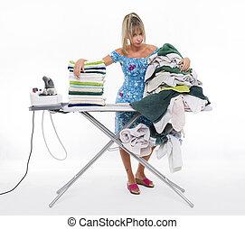 Woman ironing on board many clothing
