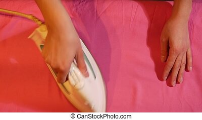 woman ironing red cloth . Top view