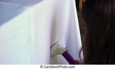 Woman ironing tablecloth with garment steamer - Woman...