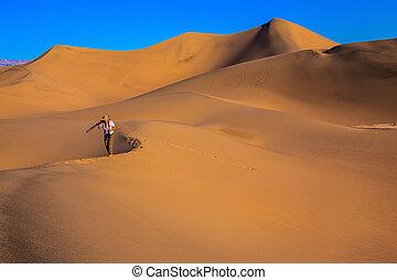 Woman is among sand dunes