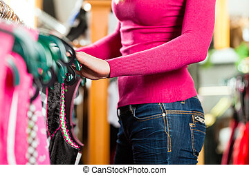 Woman is buying Tracht or dirndl in a shop - Traditional...