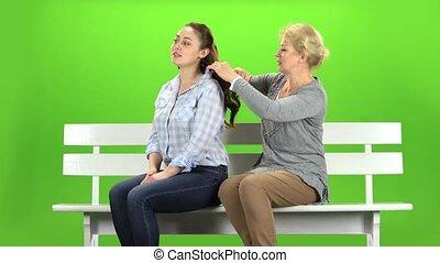 Woman is combing her daughter. Green screen