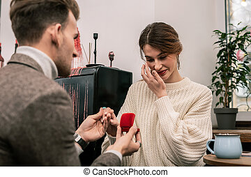 Woman is crying while receiving a proposal from her partner