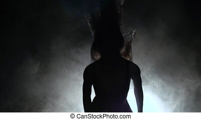 Woman is dancing a sexy dance in the smoke. Black background. Silhouette