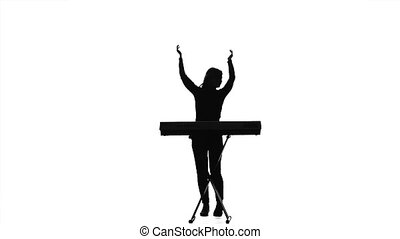 Woman is dancing for the electronic piano. Silhouette. Studio