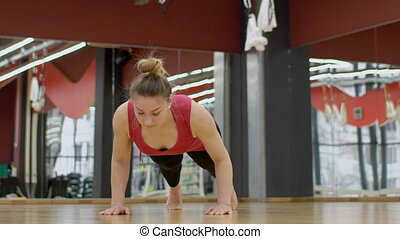 Woman is doing an exercise plank with a deviation back in...