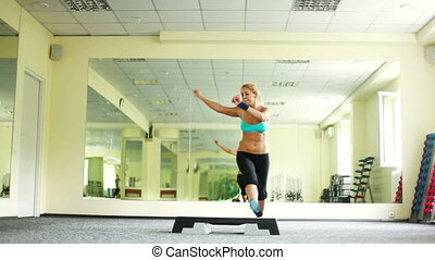 Woman is doing exercises with Step
