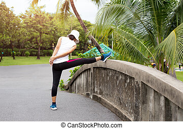 Woman is doing stretching on the bridge in a park in the morning.