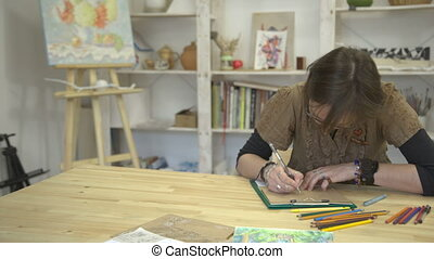 Woman is drawing picture or card sitting at desk with...