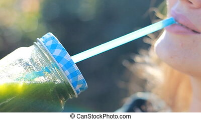 Woman is drinking green smoothies close-up. Concept of...