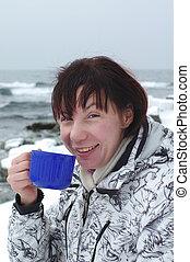 woman is drinking hot tea