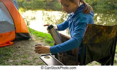 Woman is drinking tea in an armchair near a tent on the river bank