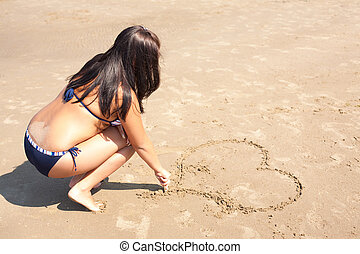 Woman is drowing a heart on the sand