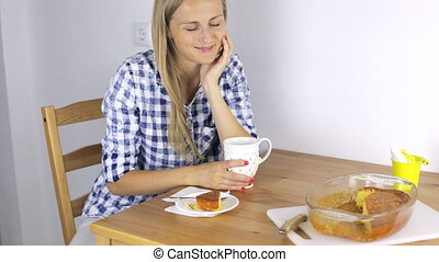 Woman is eating breakfast and watching TV