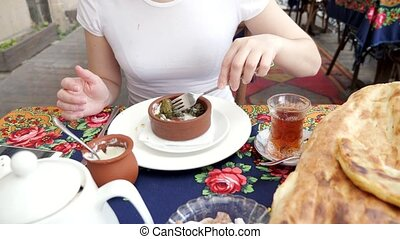 Woman is eating dolma with sour cream in traditional ...