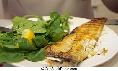 Woman is eating frying fish with green leaves sitting in...