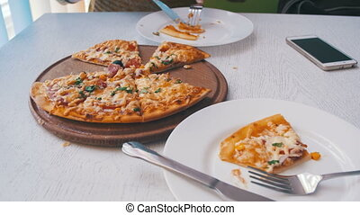 Woman is Eating Pizza in a Cafe with a Mobile Phone on a White Stylish Wooden Table