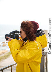 Woman is engaged in photography - Young mulatte woman in...
