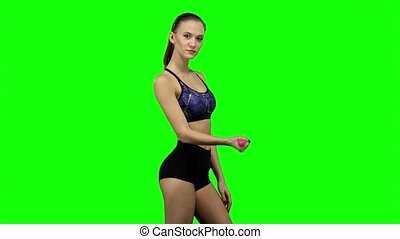 Woman is engaged with weights in one hand. Green screen