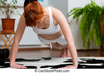 Woman is exercising at home