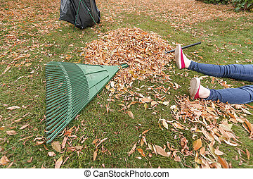Woman is exhausted from raking leaves.