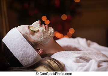 woman is getting facial clay mask at spa
