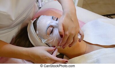 Woman is getting facial mask and rejuvenation procedure for...