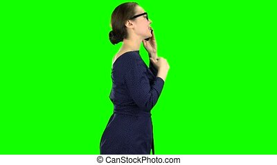 Woman is going to a meeting and talking on the phone. Green screen. Side view