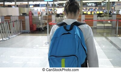Woman is going to the registration desk in airport terminal, back view.