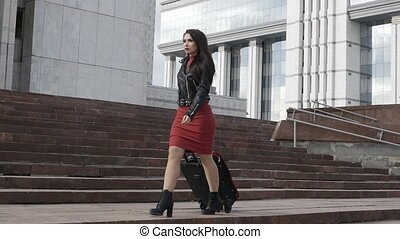 Woman is going with red suitcase