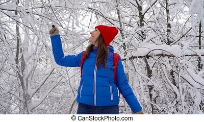 Woman is having fun - she is shaking the branches of a tree and snow is falling on her. Clear sunny frosty weather. Slow motion