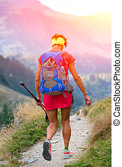 Woman is hiking in the mountain path