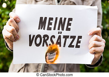 Woman is holding a burning paper with german text